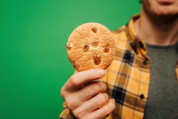 Close-up jonge man houdt koekje