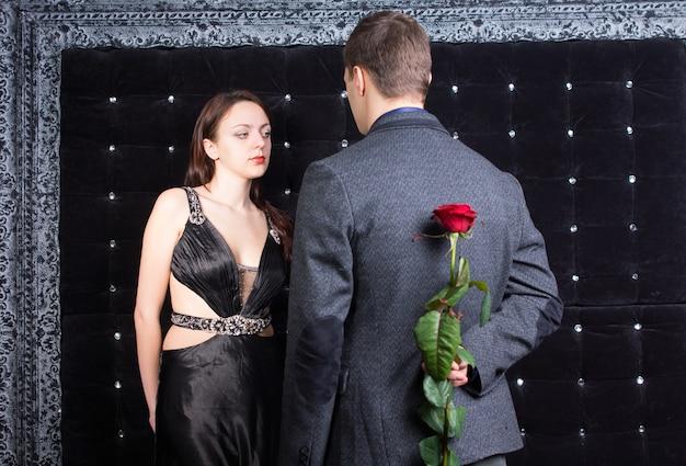 Close-up jonge man in gesprek met een mooie dame, in sexy zwarte jurk, met rood roze bloem op zijn rug. gevangen op sprankelende zwarte achtergrond.
