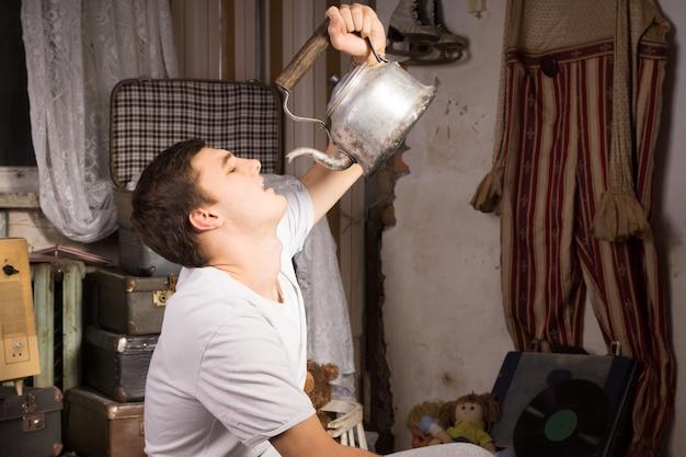 Close-up jonge man in wit overhemd iets drinken uit vintage waterkoker op de junk room.
