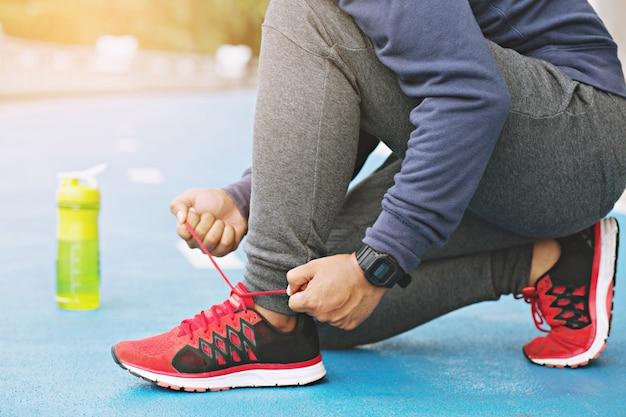 Close-up jonge man runner koppelverkoop schoenveters zitten op trappen, gezonde levensstijl en sport concepten.