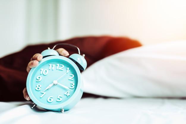 Close-up jonge slaapvrouw en stijgingshand om wekker in de slaapkamer thuis uit te zetten.