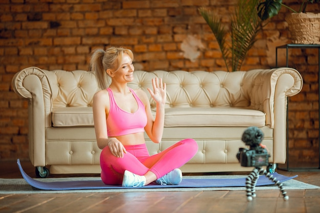 Close-up jonge sportieve fit slanke vrouw coach oefent video online training yoga-instructeur