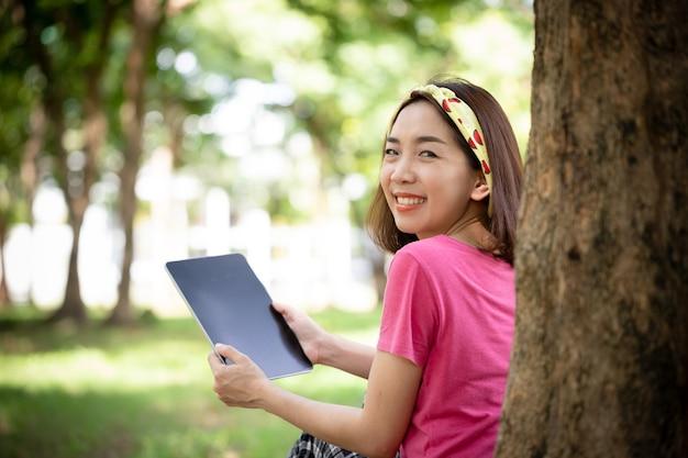 Close-up, jonge sportvrouw met behulp van tablet in het park om te ontspannen na het werken
