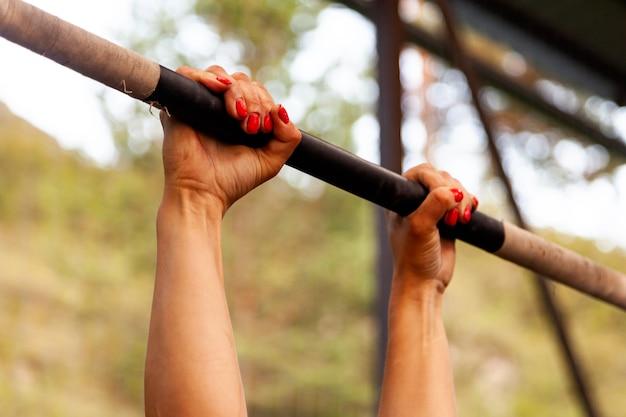 Close-up jonge vrouw die aan de dwarsbalk hangt voor pull-ups, handen in magnesiumoxide tegen de achtergrond van de sportschool