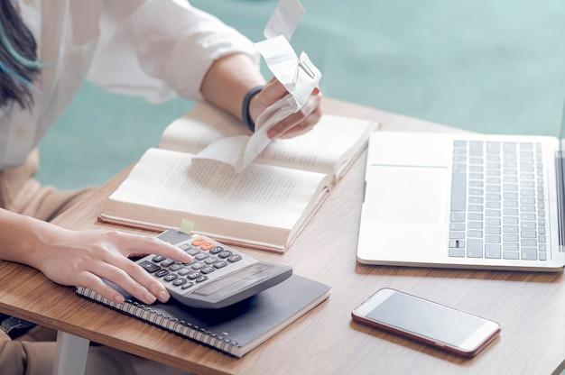 Close-up jonge vrouw die boekhoudingsbegroting berekenen, een ontvangstbewijs houden gebruikend calculator en zittend op bank in de woonkamer.