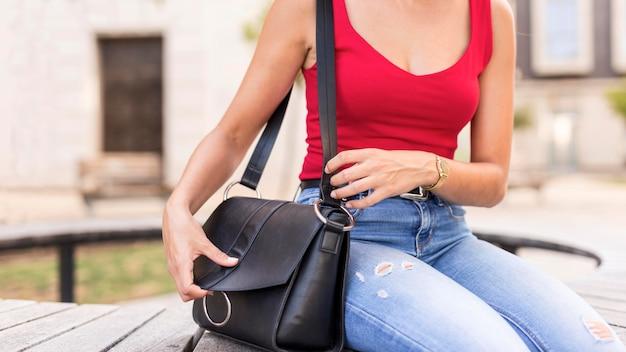 Close-up jonge vrouw die handtas controleert