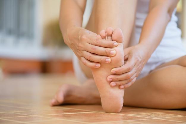 Close-up jonge vrouw die pijn in haar voet thuis voelt. gezondheidszorg en medisch concept.