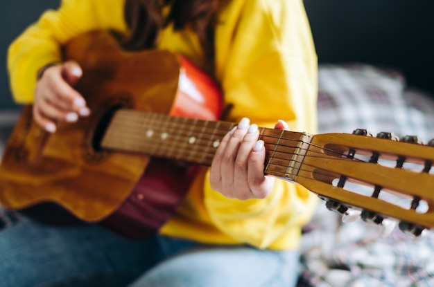 Close-up jonge vrouw hand akoestische gitaar thuis spelen.