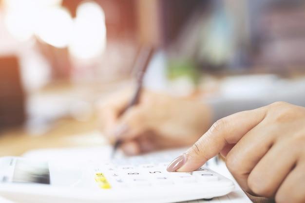 Close-up jonge vrouw hand is schrijven in een notitieblok en met behulp van rekenmachine tellen maken van notities boekhouding op het doen van financiën thuis kantoor.