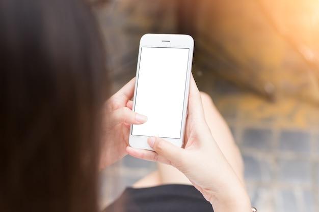 Close-up jonge vrouw houd mobiele telefoon geïsoleerd wit scherm voor reclame weergave