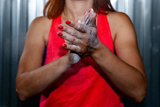 Close-up jonge vrouw in roze top smeert handen met magnesia voor de training tegen een grijze muur achtergrond