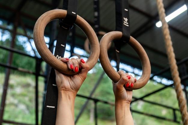 Close-up jonge vrouw opknoping op gym ringen, handen in magnesiumoxide tegen de achtergrond van gym
