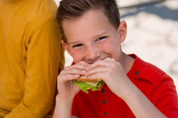 Close-up jongen die sandwich eet