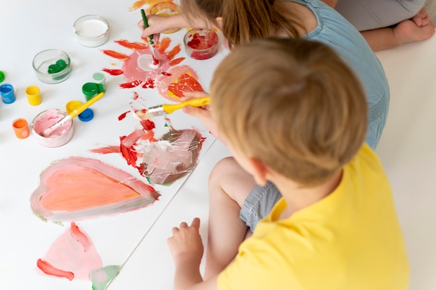 Close-up jongen en meisje samen schilderen