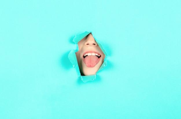 Close-up jongen gezicht toont haar tong. kind stak haar tong uit door een gat in het papier