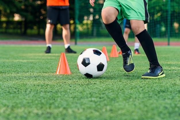 Close-up jongen in sportkleding traint voetbal op voetbalveld en leert de bal ertussen te cirkelen