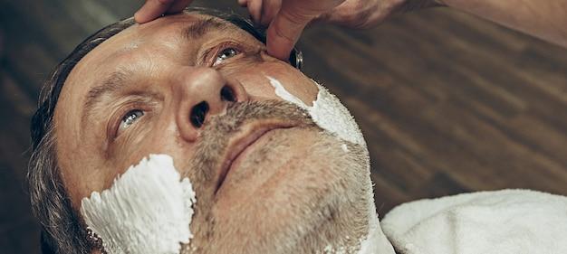 Close-up kant bovenaanzicht knappe senior bebaarde blanke man krijgt baard verzorgen in moderne kapsalon.