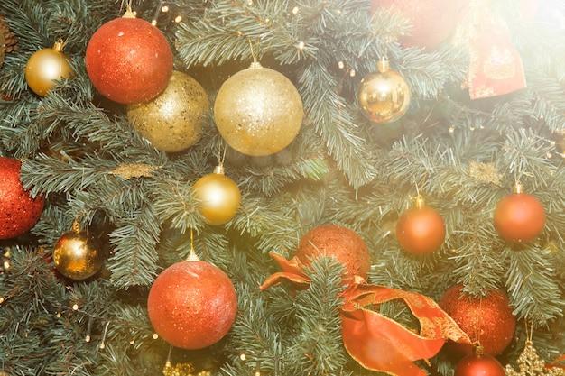 Close-up kerstvakantie achtergrond van versierde boom met kerstballen en speelgoed. concept van het vieren van gelukkig nieuwjaar. decor of in huis interieur. ruimte voor site kopiëren