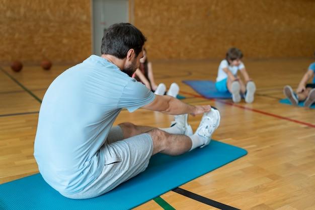 Close-up kinderen en leraar stretching