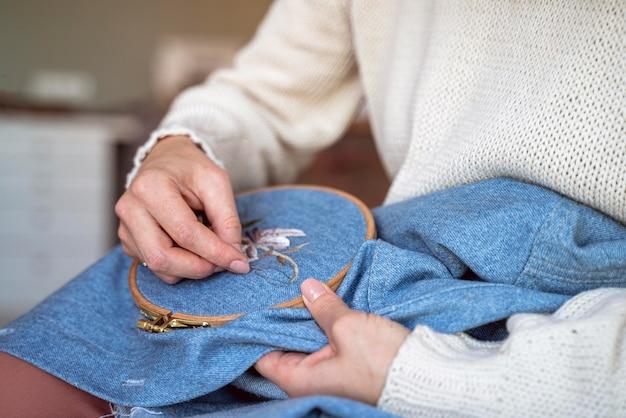 Close-up kleermakershanden die met naalden werken