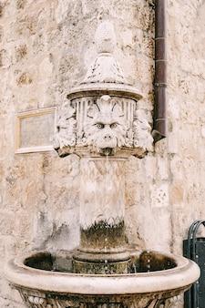 Close-up kleine fontein op de hoek van het gebouw op een plein in de oude stad van dubrovnik