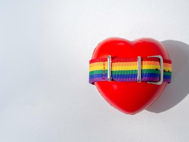 Close-up kleine regenboogvlag riem op rood hart bal geïsoleerd op een witte achtergrond met kopie ruimte. lgbt-concept met trotskleuren en regenboogvlagstrook.