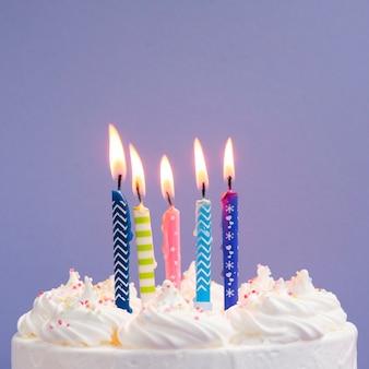 Close-up kleurrijke kaarsen op heerlijke cake