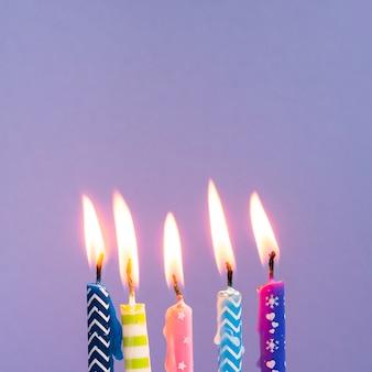 Close-up kleurrijke kaarsen op purpere achtergrond