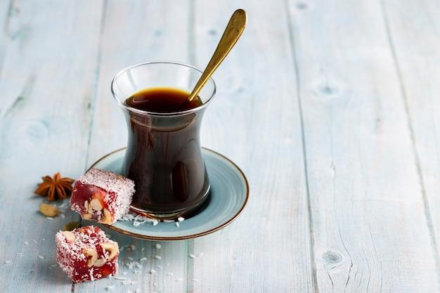 Close-up koffie glas met snoep op tafel