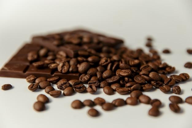 Close-up koffiebonen en chocolade op een witte achtergrond.