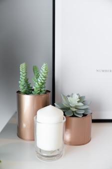 Close-up koperen vaas met kunstmatige plant binnen en witte kaars in glas op crème gespoten werktafel met grijs geschilderde muur