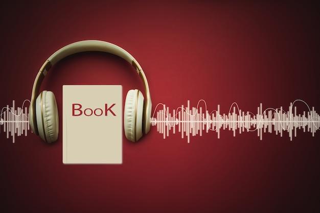 Close-up koptelefoon en audioboek op rode achtergrond met audiotrack. geluid, luister. audioboek-concept.