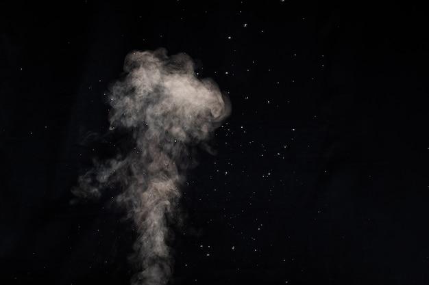 Close-up krullen van stoom of rook met druppels vocht geïsoleerd op zwarte achtergrond, low key, kopieer ruimte. duidelijke eenvoudige sjabloon voor ontwerp