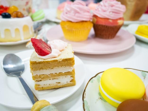 Close-up kunstmatige cake of nep cupcake op witte schotel met verschillende desserts en cake