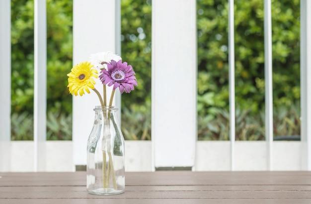 Close-up kunstmatige kleurrijke bloem op transparante glasfles op houten stoel op de achtergrond van de tuinmening