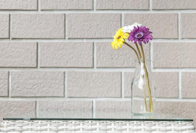 Close-up kunstmatige kleurrijke bloem op transparante glasfles op houten weefsellijst