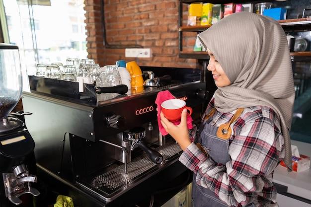 Close-up lachende barista klaar om een glas voor de klant in een café te bereiden