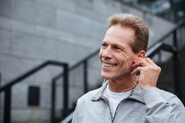 Close-up lachende loper in grijze sportkleding met koptelefoon staande op trappen en wegkijken