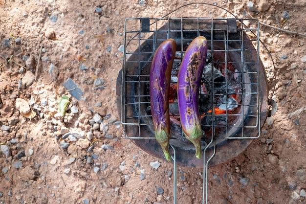 Close-up lange groene aubergines barbecue gegrild op hete houtskool. concept gezondheid. folk leven.