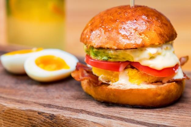 Close-up lange smakelijke hamburger met kaas, tomaten en omelet