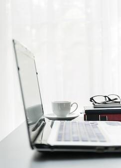 Close-up laptop geplaatst op desktop met koffiekopje en bril op boek in kamer thuis kantoor