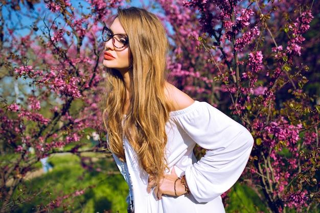 Close-up lente zomer portret van prachtige jonge vrouw met natuurlijke verbazingwekkende lange haren en schoonheid gezicht, heldere bril, zonnige kleuren.