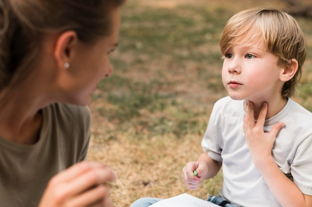 Close-up leraar en jongen buitenshuis