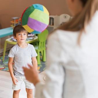Close-up leraar en jongen spelen met bal