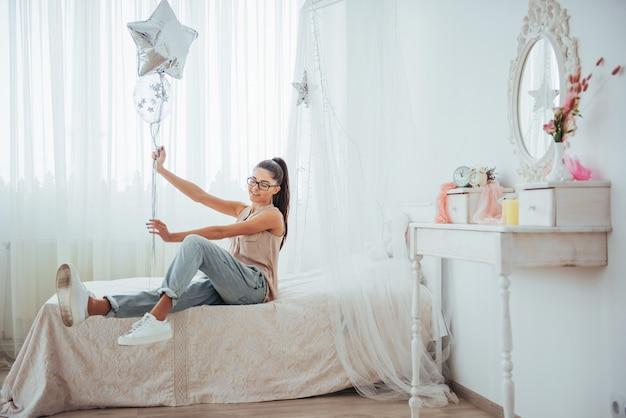 Close-up leuk donkerbruin meisje in, breed glimlachend en speel met transparante en zilveren ballons. ze draagt een bril en verwrongen haar.