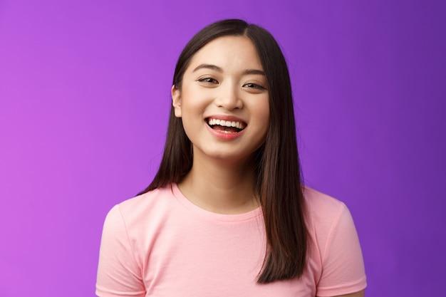 Close-up levendig zorgeloos vrolijk aziatisch meisje lachen, plezier maken, geamuseerd glimlachen genieten van een vriendelijk ontspannend gesprek, staan paarse backgrond vrolijk, kijk camera vrolijk. ruimte kopiëren