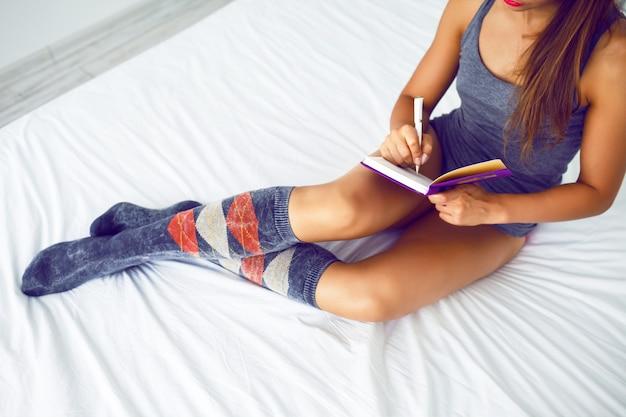 Close-up levensstijl beeld van jonge vrouw tot op het bed en belangrijke aantekeningen maken in haar dagboek. felle kleuren.