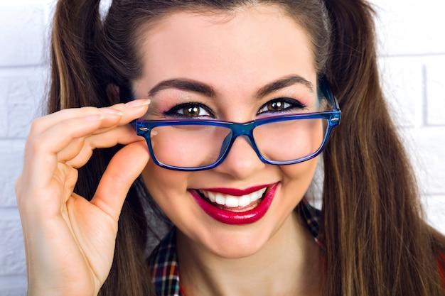 Close-up levensstijl mode portret van jonge hipster vrouw met lichte make-up en verbazingwekkende pluizige brunette haren, glimlachend. mooie vrouw met grote lichtbruine ogen.