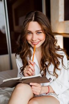 Close-up levensstijl portret van jonge vrouw in wit overhemd glimlachen