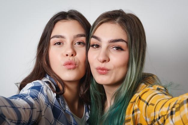 Close-up levensstijl selfie portret van twee jonge positieve vrouw met plezier en het maken van selfie, trendy hipster tiener kleding en verse make-up